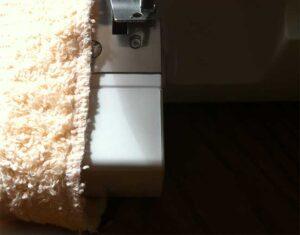 Overlock stitch on frayed towel